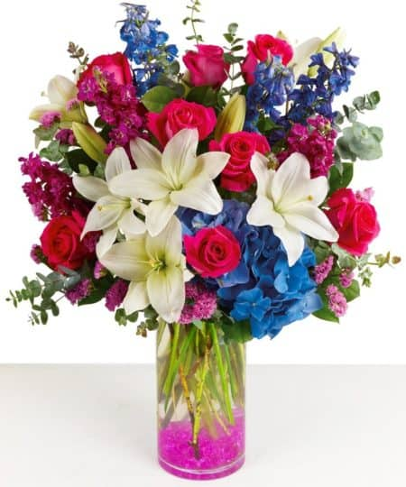 lovely bouquet is arranged in a tall slender glass vase with magenta hues throughout in accenting gems, Stock, Roses, and Statice. Also, designed with Lilies, Blue Hydrangeas, Delphinium with a garden feel greenery like Eucalyptus.